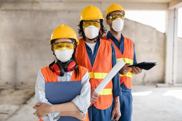 colleagues-with-safety-equipment-working-with-blueprints_23-2148908431